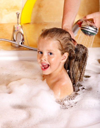 Kid washing hair by shampoo .