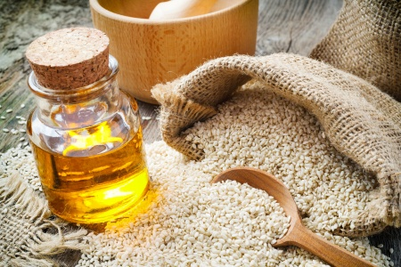 sesame seeds in sack and bottle of oil on rustic table